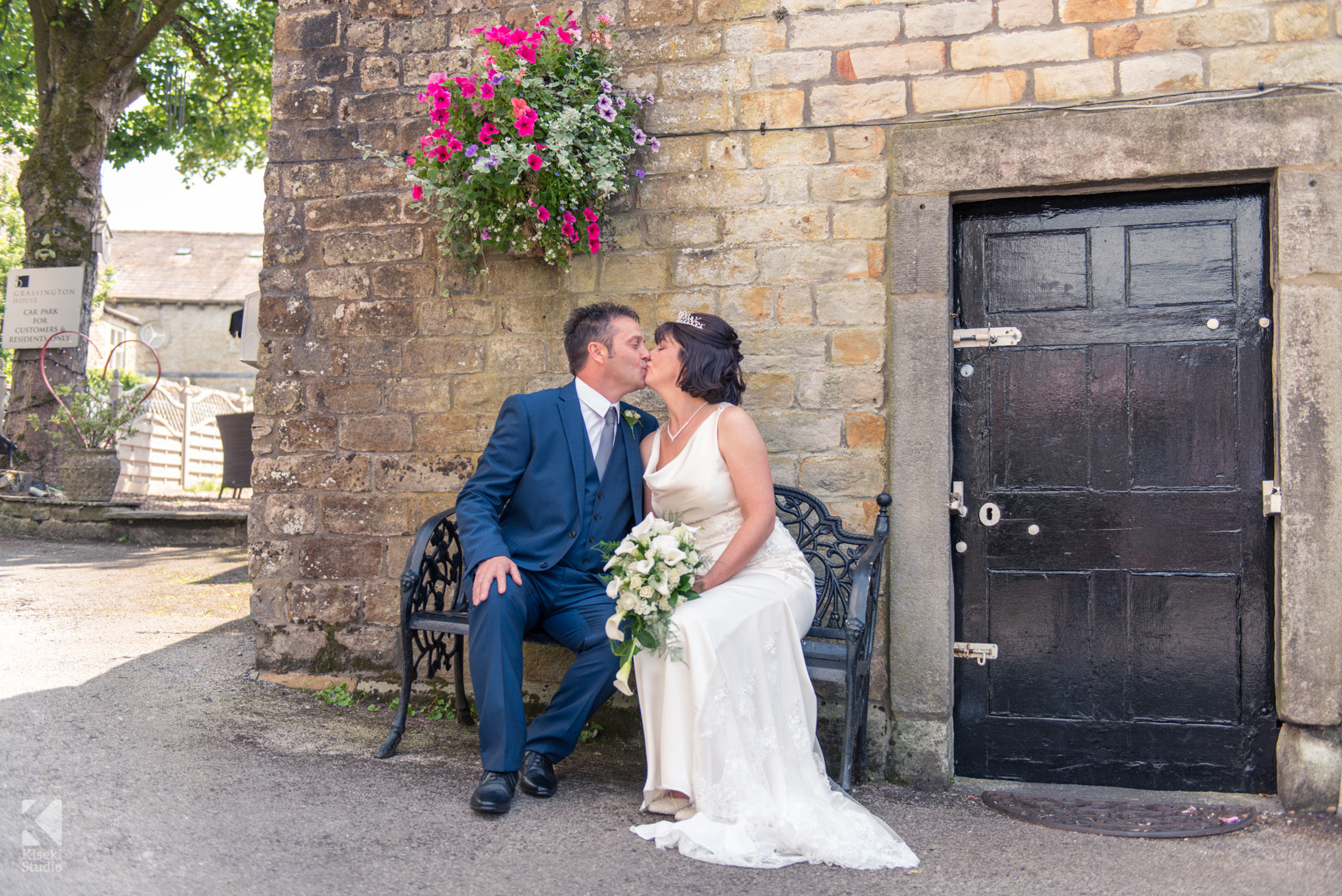 Bride and Groom enjoying a kiss on a bench