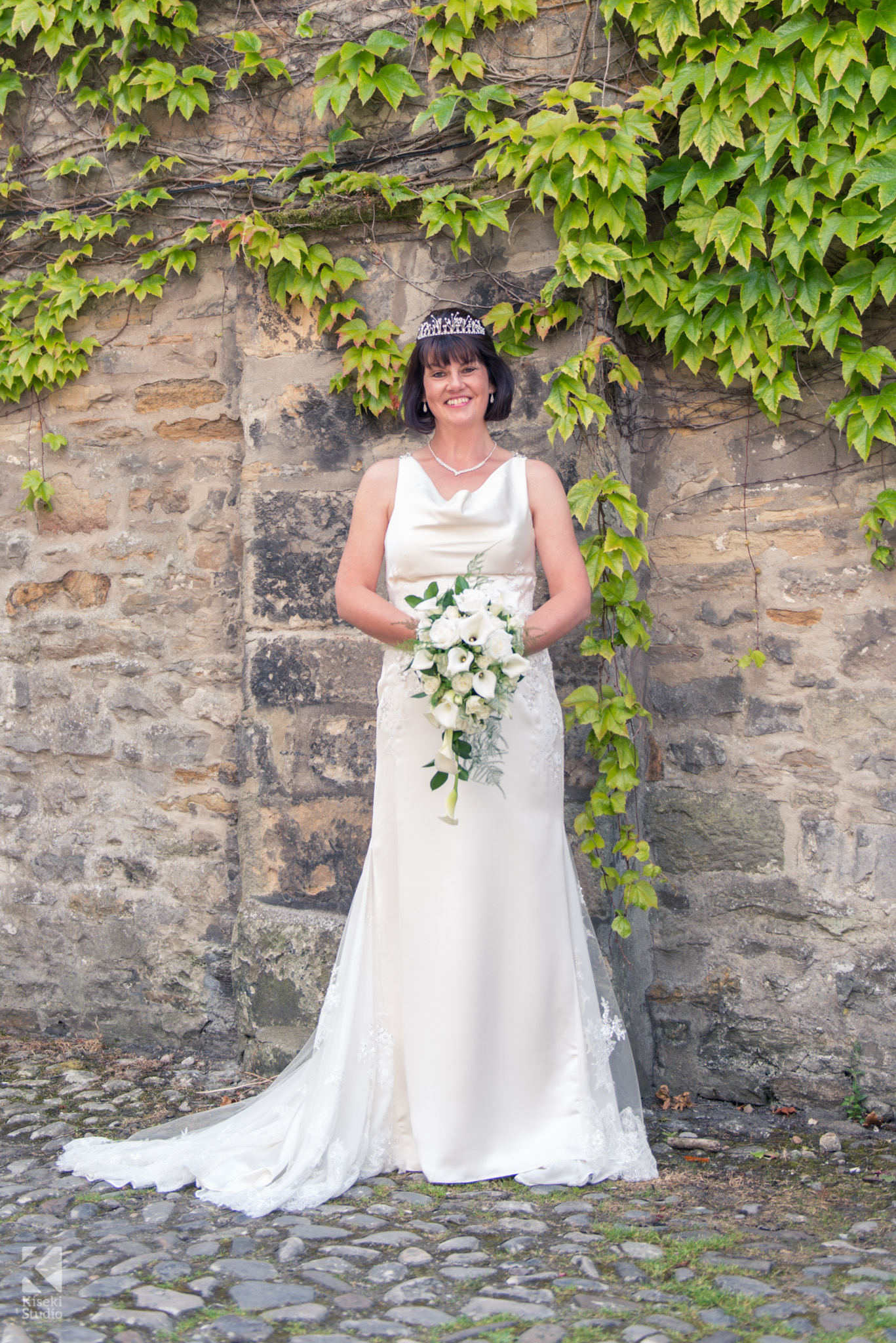 Bride standing next to ivy outside in her white dress