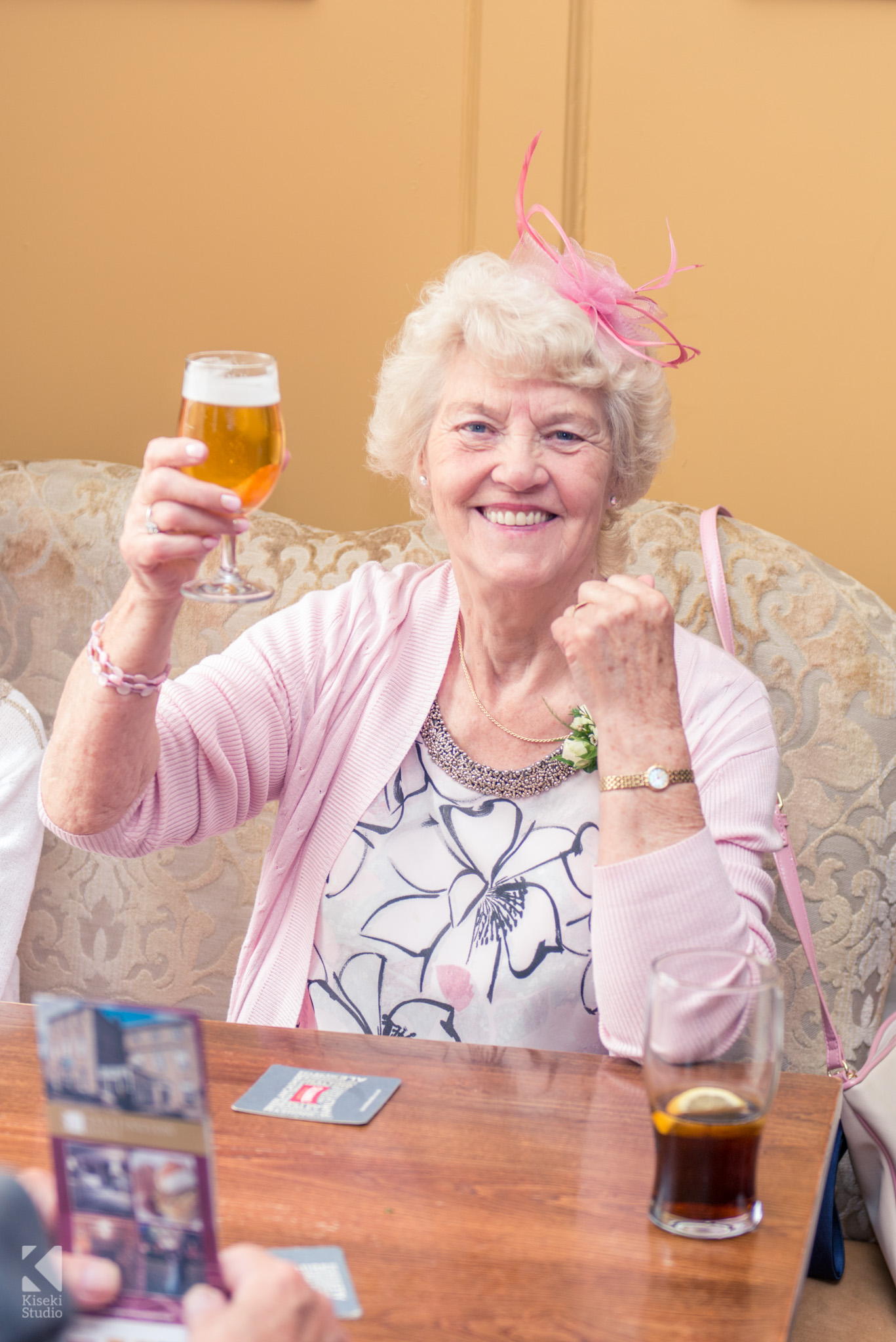 Brides mother raising her beer glass in joy
