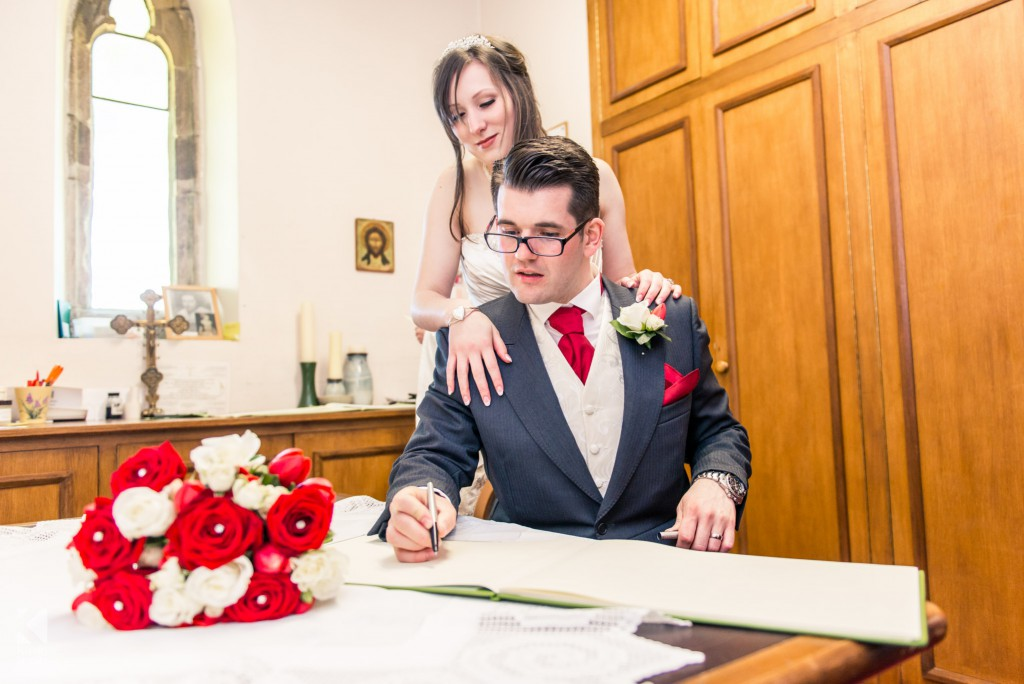 The bride and groom sign the register