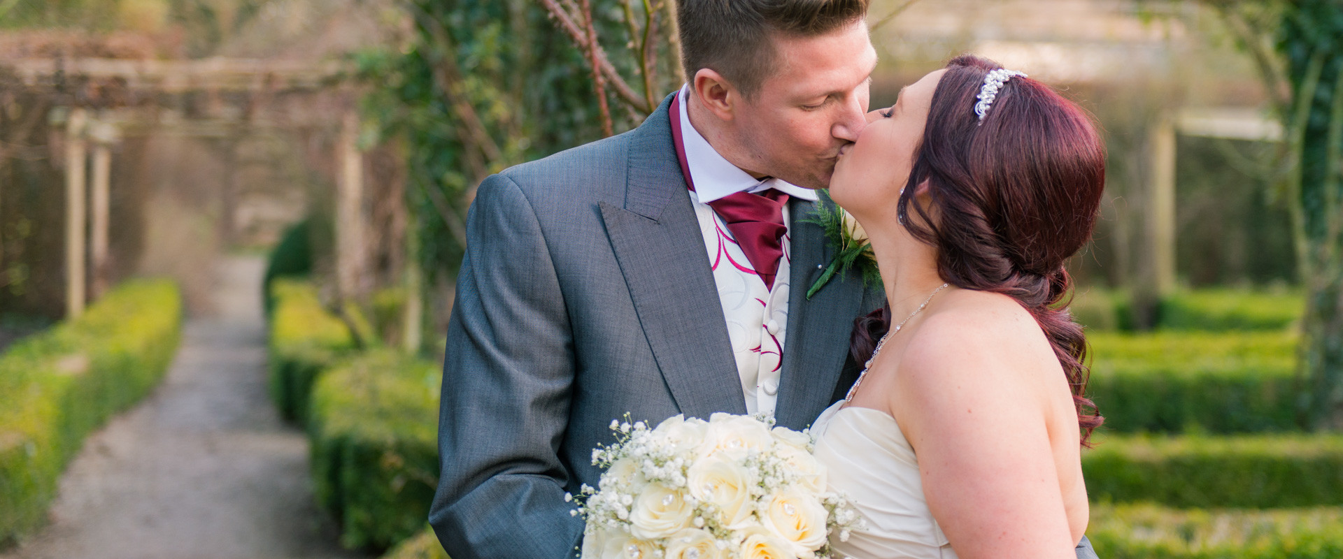Ripley Castle Wedding - Bride and Groom kissing in the garden